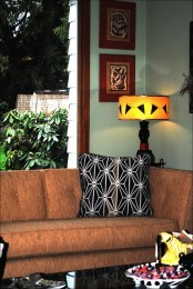 a cozy mid-century modern living room with touches of African and Asian cultures and greenery