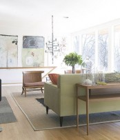 a pastel mid-century modern living room with pastel green and beige furniture, artworks and a chandelier