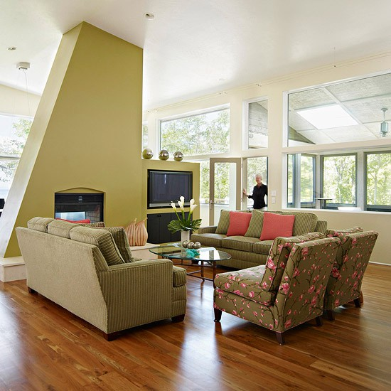 a bright mid-century modern living room done in green, with floral chairs, a built-in fireplace and TV