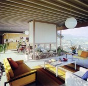 a neutral mid-century modern living room with yellow furniture, lots of greenery and a large panoramic view
