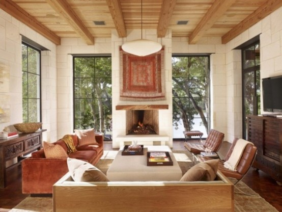 a cozy neutral and brown living room with wooden beams and a ceiling, leather chairs, dark and light stained furniture