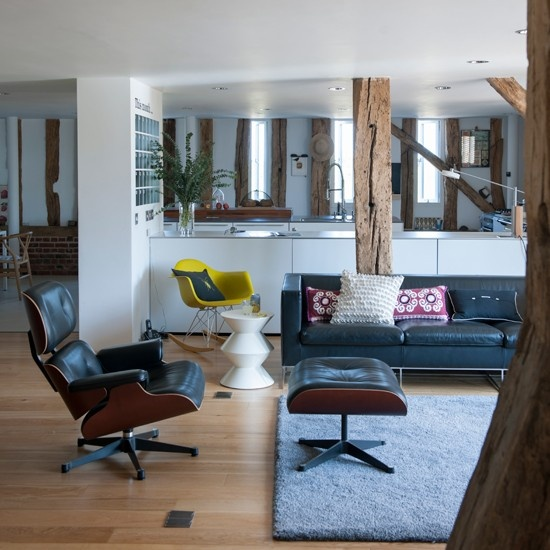 a mid-century modern meets rustic living room with black leather furniture, wooden beams and bright  touches