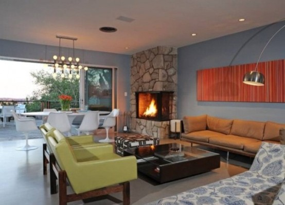 a welcoming mid-century modern living room with green chairs, bright artworks, a built-in fireplace and lots of lamps