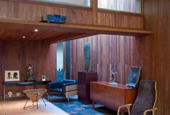 a cozy mid-century modern living space with stained wood that covers everything, stylish furniture and artworks