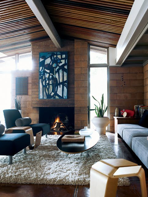 a mid-century modern living room with large bricks, navy and grey furniture, a fireplace and an abstract artwork