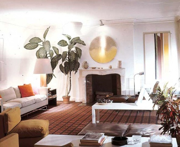 an airy living room with white furniture, a faux fireplace, potted greenery and leather touches