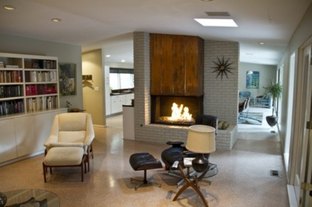 an airy living room with a built in fireplace, creamy and black furniture, a built in bookcase and elegant decor
