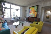 concrete walls, floor and ceiling are complemented with colorful furniture and bright artworks