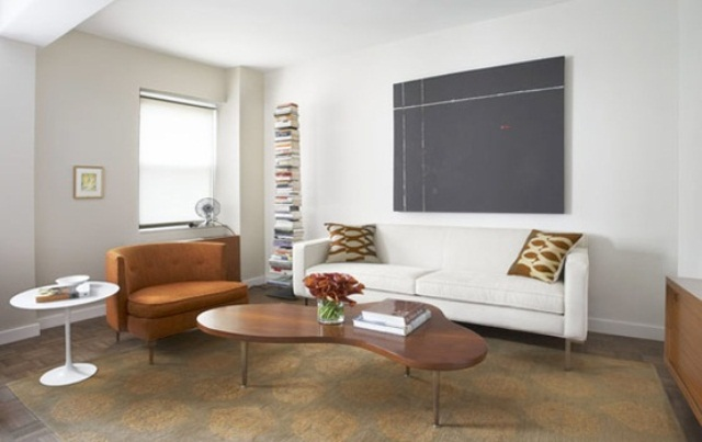 a neutral and airy living room with brown furniture, a creamy sofa, a stack of book and an artwork