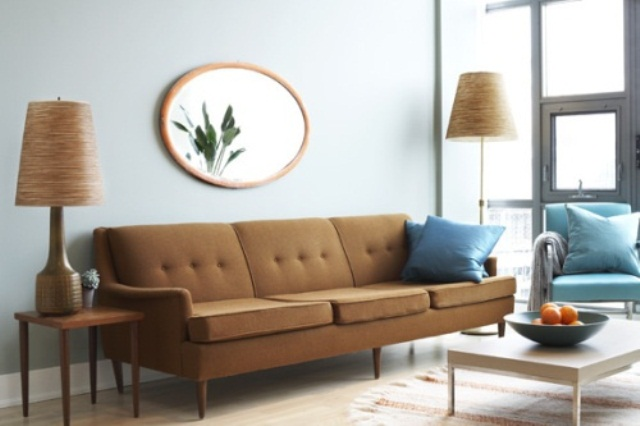 a welcoming living room done with blue and brown furniture and pillows, lamps and a mirror