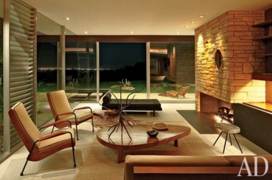 a cozy mid-century modern living room with a fireplace clad with faux stone, stylish furniture and a view