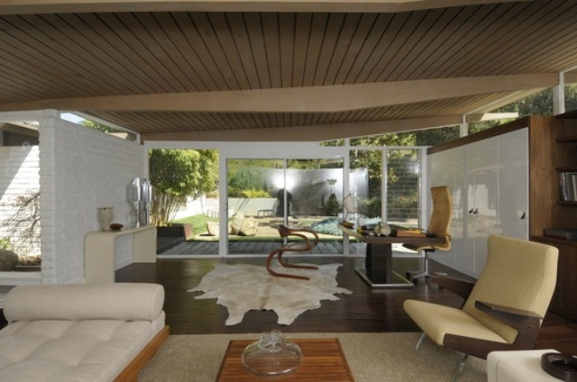 a neutral living room with creamy furniture, a faux animal skin, a wooden slab ceiling and sleek panels