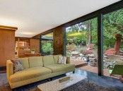 a bright mid-century modern living room with a green sofa, a terrazzo table and a fluffy rug