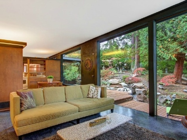 a bright mid century modern living room with a green sofa, a terrazzo table and a fluffy rug