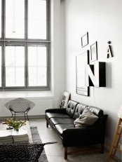 a Nordic meets mid-century living room done in a monochromatic color scheme and a cool gallery wall