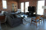 an industrial space with brick walls and elegant mid-century modern furniture plus lamps