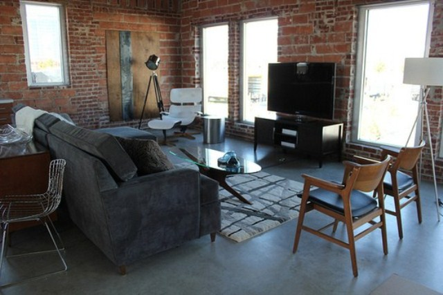an industrial space with brick walls and elegant mid century modern furniture plus lamps
