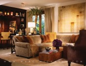 a warm-colored living room with wooden and leather furniture, ambient lights and a home bar space