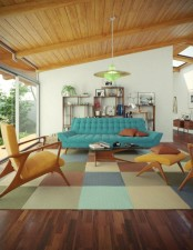 a bright living room with a blue sofa, a colorful plaid rug, bright chairs and lamps and a cool wall unit