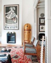 a mid-century modern living room with a printed rug, artworks and a built-in fireplace and cozy chairs