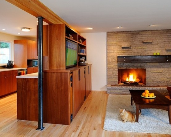 a welcoming living room with a faux stone wall, a built-in fireplace, a stained wooden furniture unit and fluffy rugs