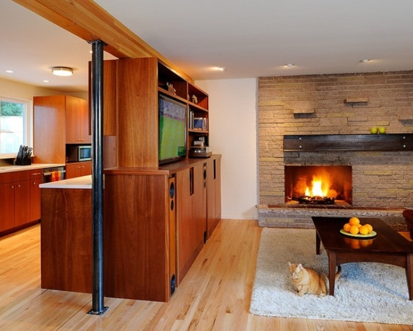 a welcoming living room with a faux stone wall, a built in fireplace, a stained wooden furniture unit and fluffy rugs