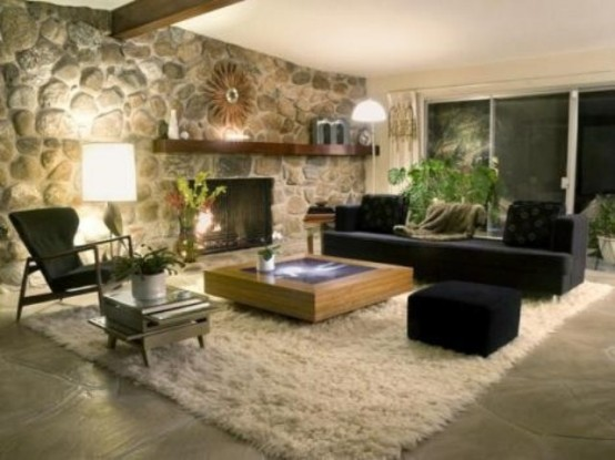 a monochromatic living room with dark furniture, a fluffy rug, a faux stone wall and a built-in fireplace