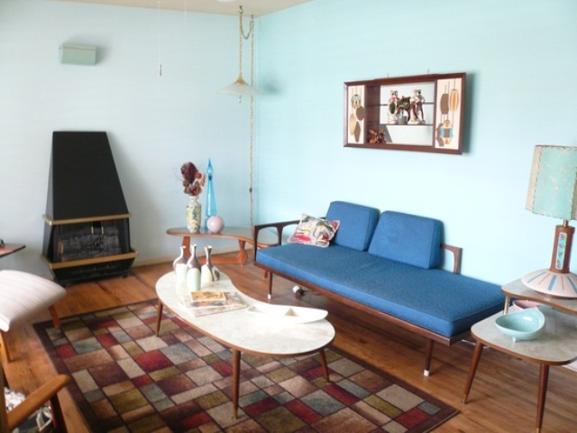a quirky mid century modern space with a blue couch, a printed rug, a heart and some unusual lamps