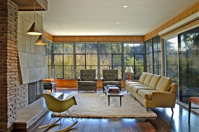 a warm colored and neutral space with yellow and grey furniture, hanging and built in lights , a fluffy rug and panoramic windows