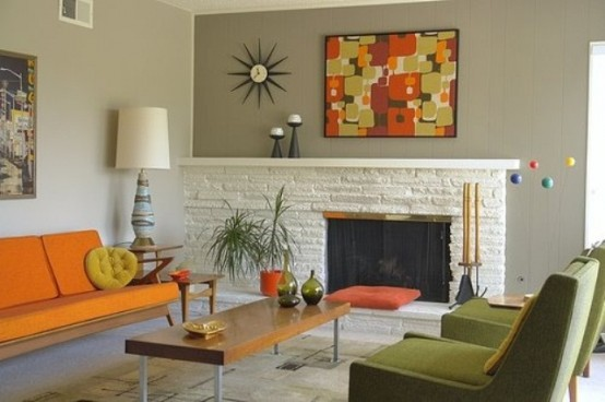 a space done in orange and green, with abstract prints, potted greenery and lamps
