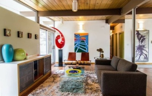 a bright mid century modern space with colorful touches   green, blue, red and yellow and a chocolate brown sofa