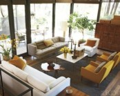 a mid-century modern living room with grey, yellow and creamy furniture, potted greenery and blooms and a stained wooden cabinet