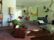 a pastel grene mid-century modern living room with dark stained furniture, potted greenery, artworks and lamps