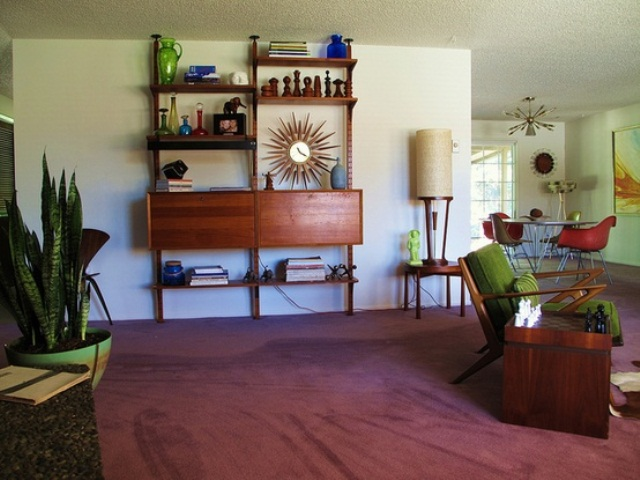 a mid century modern space with a mauve rug, dark staiend furniture and potted plants