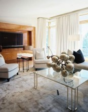 a creamy living room with a glass table, upholstered furniture, creamy curtains and a plywood clad wall with a TV