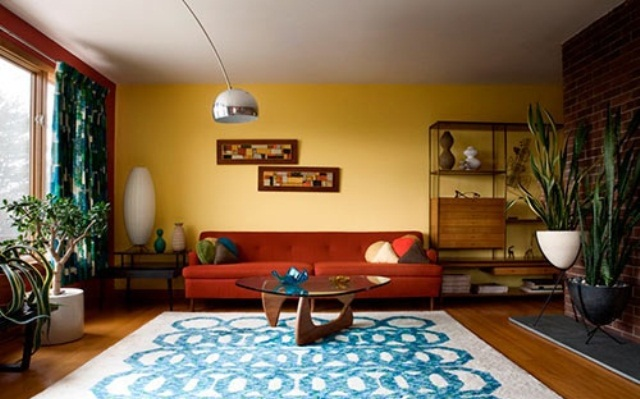 a colorful mid century modern living room with a yellow and brick wall, printed textiles and potted plants