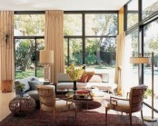an airy living room with views, creamy and grey furniture, elegant floor lamps and potted blooms and greenery
