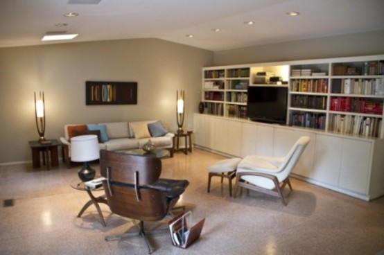 a white mid-century modern living room with a built-in bookcase, cremay furniture, elegant lamps and a chic artwork