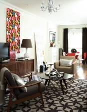a monochromatic living room done with touches of red and prints, with dark stained furniture and a chic chandelier