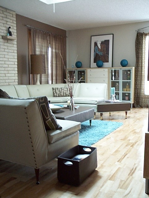 a neutral living room spruced up with blue and brown touches, with some prints and faux brick plus artworks