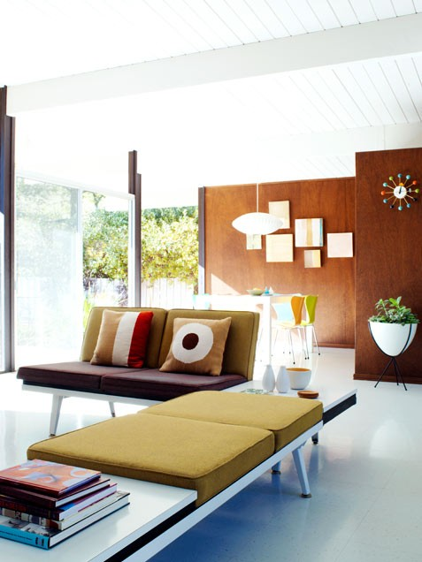 a bright living room with plywood walls, a mustard couch, lots of natural light and a gallery wall