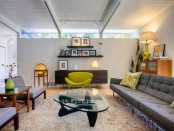 a cozy living room with grey furniture, touches of neon green and dark stained items and a skylight