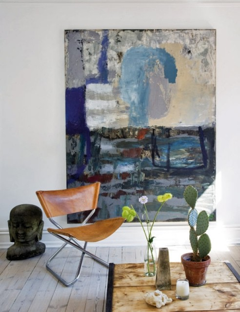 a fantastic nook with a leather butterfly chair, a statement artwork, potted cacti and natural light