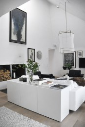a monochromatic Nordic living room with black and white furniture, pendant lamps and firewood storage for more coziness