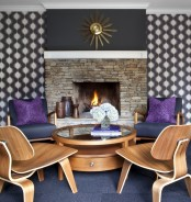 a mid-century modern living room with a built-in fireplace, printed wallpaper and catchy plywood furniture and a sunburst clock