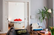 a bright mid-century modern living room with colorful furniture, potted greenery and lamps