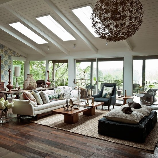 a cozy boho meets mid-century modern living room with dark and neutral furniture, skylights, wooden tables and much natural light