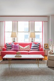 a colorful living room with a pink sofa, pink edging and curtains, a printed rug and cozy furniture