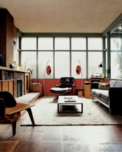 a mid-century modern living room with bright orange and yellow touches, dark touches, faux brick, plywood and cork touches