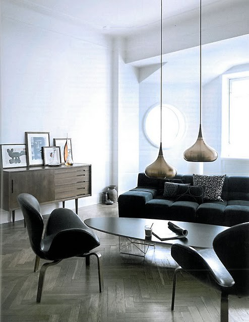 a monochromatic living room with suspended lamps, dark furniture, wood clad floor and a round window